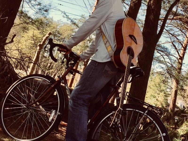 Man on a bicycle with guitar