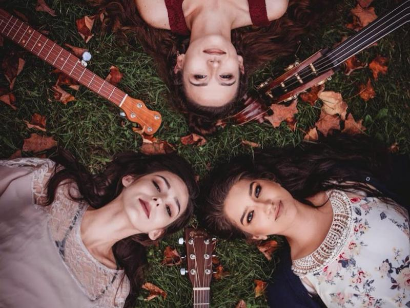 3 girls lying on the ground with their insturments