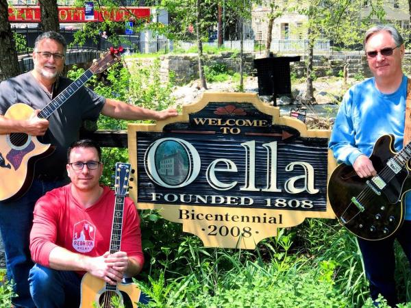 3 guys by the oella sign